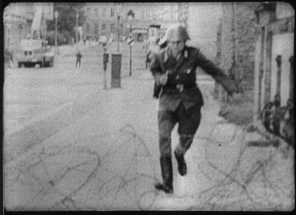Police officer jumping over barbed wires during the tension period.