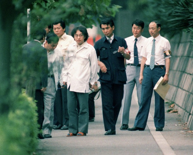 Child killer Tsutomu Miyazaki, wearing glasses at centre left, assists police at a crime scene in 1989.